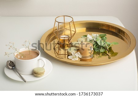 Breakfast is served with flowers,  cup of coffee and dessert. Interior of the living room with a coffee table. A Cup of coffee on a gold tray, a candle. Still life with home interior and comfor #1736173037
