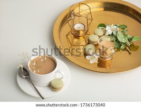 Breakfast is served with flowers,  cup of coffee and dessert. Interior of the living room with a coffee table. A Cup of coffee on a gold tray, a candle. Still life with home interior and comfor #1736173040