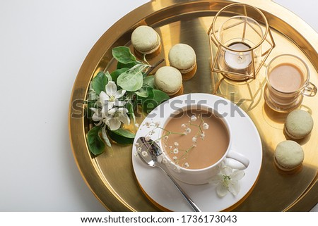 Breakfast is served with flowers,  cup of coffee and dessert. Interior of the living room with a coffee table. A Cup of coffee on a gold tray, a candle. Still life with home interior and comfor #1736173043