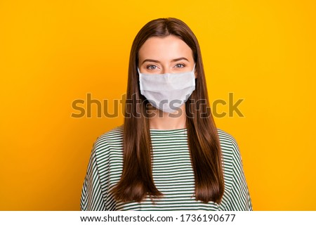 Photo of girl standing in front of camera and trying not to blink keep social distance wear medical mask isolated with yellow background #1736190677