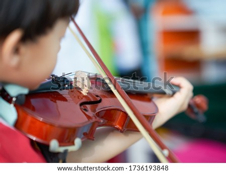 boy plays violin with bow string with copy space on blur background,selective focus Royalty-Free Stock Photo #1736193848