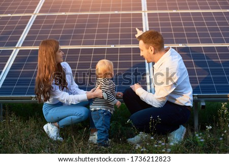 Father shows his family the solar panels on the plot near the house during a warm day. A young girl with a child and a man in the sun rays look at the solar panels. #1736212823