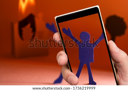 Man on screen of smartphone. Fire and man with hands up. #1736219999