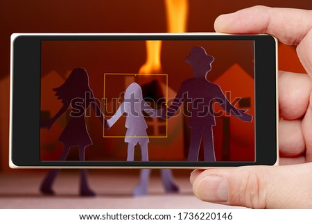 Fire on smartphone screen. Family at burning house. #1736220146