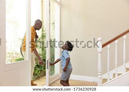 Side view of an African American man arriving home, welcomed by his young son opening the front door. Social distancing and self isolation in quarantine lockdown for Coronavirus Covid19 Royalty-Free Stock Photo #1736230928