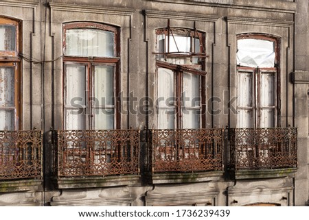 Exterior of a vintage derelict apartment building. Facade of an abandoned historical house in Porto, in need of restoration. False balconies or balconets are common in Portugal. Royalty-Free Stock Photo #1736239439