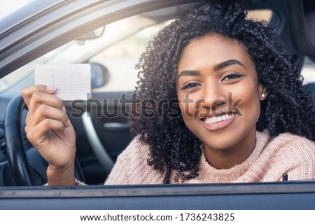 Happy black woman driving her new car holding car license #1736243825
