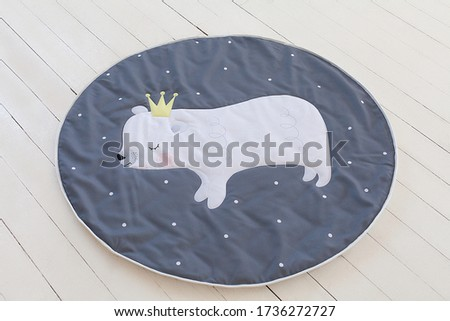 A circle carpet as a decorative element in design of a baby room on a white wooden background with a picture of a polar bear