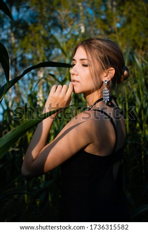 Close-up of young woman in black dress, necklace and earrings between green leaves in a corn field in summer. Jewelry fashion style photo session. #1736315582
