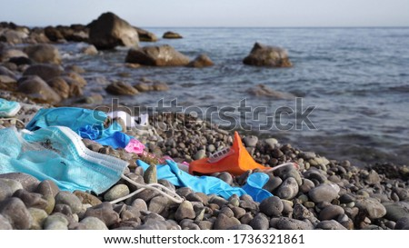 Waste during COVID-19. Discarded to ocean coronavirus single-use face masks and usesd latex gloves. Environmental and ocean plastic pollution Royalty-Free Stock Photo #1736321861