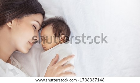 Close up portrait of beautiful young asian or caucasian mother girl kissing her healthy newborn baby sleep in bed with copy space. Healthcare and medical love asia woman lifestyle mother's day concept #1736337146