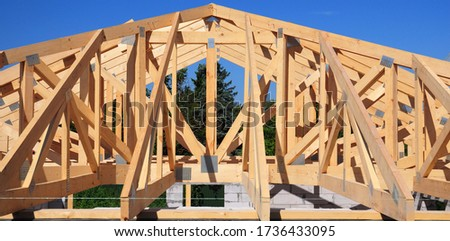 Unfinished roofing wooden frame house construction with roof beams, trusses, timber, braces and eaves of a brick house building against blue sky and forest.  #1736433095