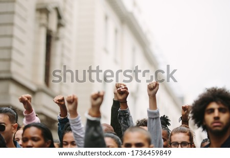 Arms raised in protest. Group of protestors fists raised up in the air. #1736459849