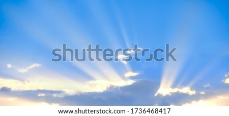Horizontal shot of background of sun rays over clouds.