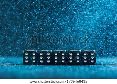 Game cubes are next to each other. Five identical black cubes on a blue background. Photo with bokeh.