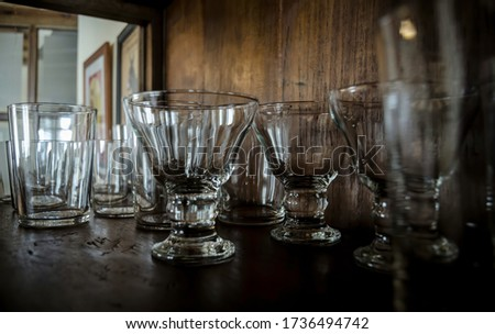 Crystal glasses in an old wooden showcase. In the background are some pictures.