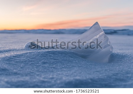 Blue ice small iceberg lies on the snow of Lake Baikal against the background of orange dawn