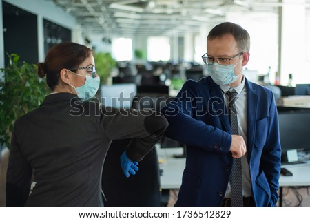 Two colleagues avoid a handshake when meeting in the office and greet bumping elbows. Greetings in Wuhan. A man and a woman in medical masks maintain a social distance at work. #1736542829