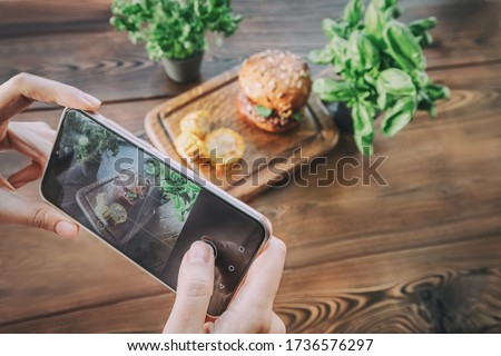 Girl food photographer and blogger takes pictures of a fast food set with Hamburger and corn chips on smartphone, then post these photos to social networks