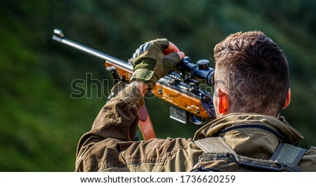 Hunting period. Male with a gun. Close up. Hunter with hunting gun and hunting form to hunt. Hunter is aiming. The man is on the hunt. Hunt hunting rifle. Hunter man. #1736620259