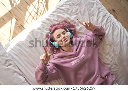 Happy funny teen girl with pink hair wear headphones lying in comfortable bed listening new pop music enjoying singing song with eyes closed relaxing in cozy bedroom at home. Top view from above. #1736626259
