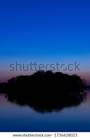 sunrise morning island silhouette vertical format of picture nature long exposure photography scenic view in twilight lighting black and dark blue colors