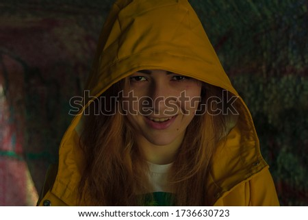 young girl scary smile Halloween concept face portrait in yellow rain coat hoodie twilight lighting in tunnel with noise pollution in picture