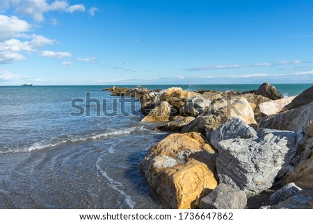 A groyne of big stones to break the waves. In the background a f #1736647862