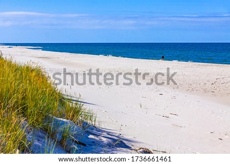 Beautiful sandy beach on Hel Peninsula, Baltic sea, Pomeranian Voivodeship, Poland. Hel is a 35-km-long sand bar peninsula in northern Poland separating the Bay of Puck from the open Baltic Sea Royalty-Free Stock Photo #1736661461
