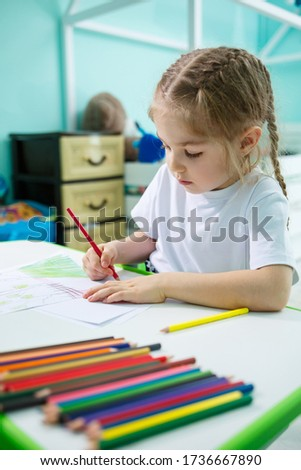 Adorable toddler girl drawing with pencils at home sitting at the table. Creative child sitting in a room learning to draw. Toddler girl doing homework at home. #1736667890