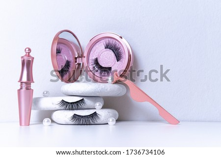 Magnetic fake artificial eyelashes in pink mirror kit, eye liner, tweezers on white background. Home eyelash extension, cosmetology tool concept, beauty treatment, improving physical appearance Royalty-Free Stock Photo #1736734106