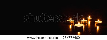 Several burning candles on a black background. Banner with copy space.