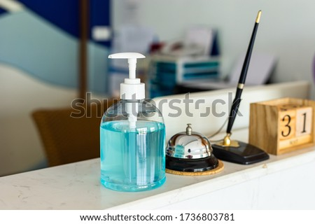 Coronavirus ( Covid-19 virus ) hand sanitizer gel or alcohol ge to wash hands at modern luxury hotel reception counter desk with bell,Pen and woodcalendar . product for airport, hospital #1736803781