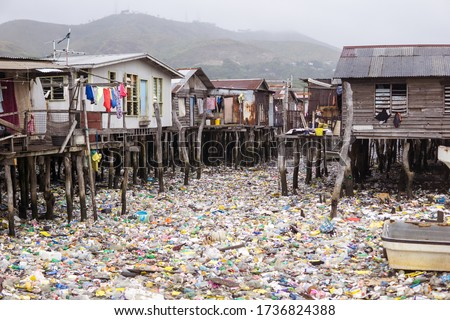 Waters filled with plastics in floating wooden village on the coast of Port Moresby, the capital of Papua New Guinea. Environmental problem, catastrophe Royalty-Free Stock Photo #1736824388