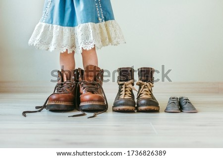 Close up of little girl putting on fathers hiking shoes. Three pairs of shoes for family indoor. Royalty-Free Stock Photo #1736826389