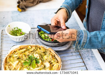 Make picture of vegan food with phone. Smartphone blogging photography of zucchini potato vegetables casserole.