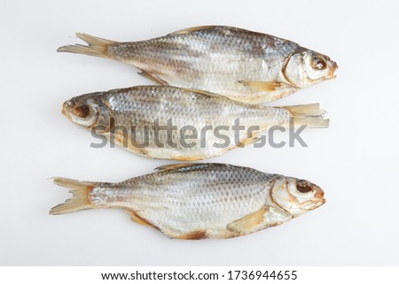 isolated close up top view shot of three Russian dried salted vobla (Caspian Roach) fish on a white background