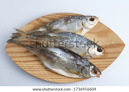isolated close up top view shot of three Russian dried salted vobla (Caspian Roach) fish on a wooden plate on a white background
