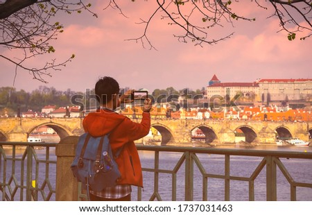 Back view of Asian Man tourist sightseeing and  traveling  lifestyle with take a picture by smartphone in Prague castle with river Vltava, Czech Republic