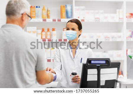 medicine, pharmaceutics, health care and people concept - apothecary wearing face protective medical mask for protection from virus disease and senior man customer buying drug at drugstore #1737055265