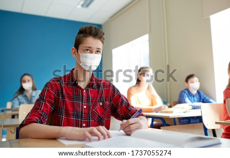 education, healthcare and pandemic concept - group of students wearing face protective medical mask for protection from virus disease with books at school lesson Royalty-Free Stock Photo #1737055274