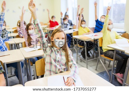 education, pandemic and health concept - group of students wearing face protective medical mask for protection from virus disease raising hands at school #1737055277