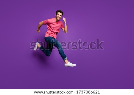 Full size profile photo of handsome attractive guy jump high up run shopping center sale prices wear casual pink t-shirt jeans footwear isolated purple color background