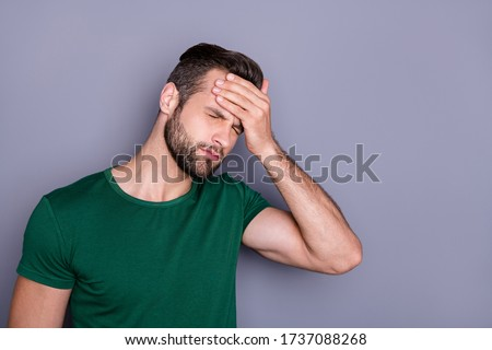 Photo of attractive handsome guy hold hand on forehead fever eyes closed grimacing caught cold corona virus temperature wear casual green t-shirt isolated grey color background