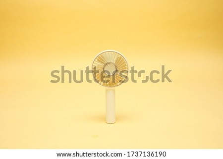 Portable mini fan on a yellow background