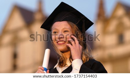 Happy pretty girl graduate in gown talking on mobile phone.