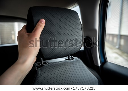 Hand adjusts leather headrest in car interior. Royalty-Free Stock Photo #1737173225