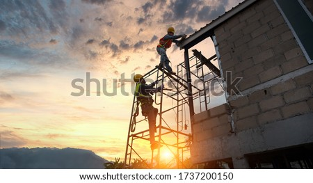 Construction workers are helping to make steel roofs Construction worker install new roof,Roofing tools,Electric drill used on new roofs with Metal Sheet. #1737200150