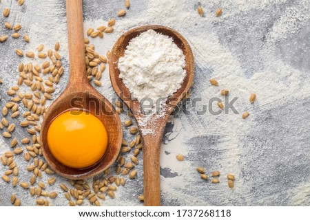 Vibrant color egg yolk and wheat flour arrangement of ingredients in two old rustic wooden spoons and wheat seeds spilled on old gray kitchen table at cooking process overhead studio shot Royalty-Free Stock Photo #1737268118
