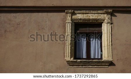 old window against brown facade background #1737292865